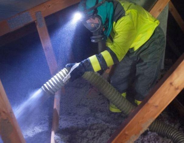 Työntekijä puhaltaa laitteella Termex-selluvilla lämmöneristettä.