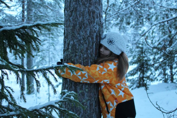 A girl hugging a tree in wintery forest.