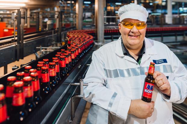 Sinebrychoff arbetare håller en Koff ölflaska.