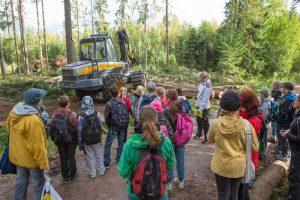 Ihmisiä katsomassa metsäkoneen toimintaa.