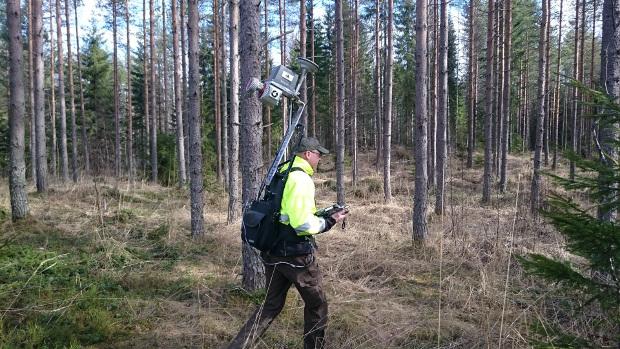 Antero Kukko reppulaserkeilaimen kanssa metsässä.