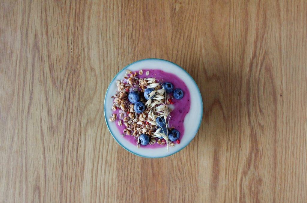 Jogurtti, joka koristeltu mustikoilla ja kaurahiutaleilla pöydän päällä.