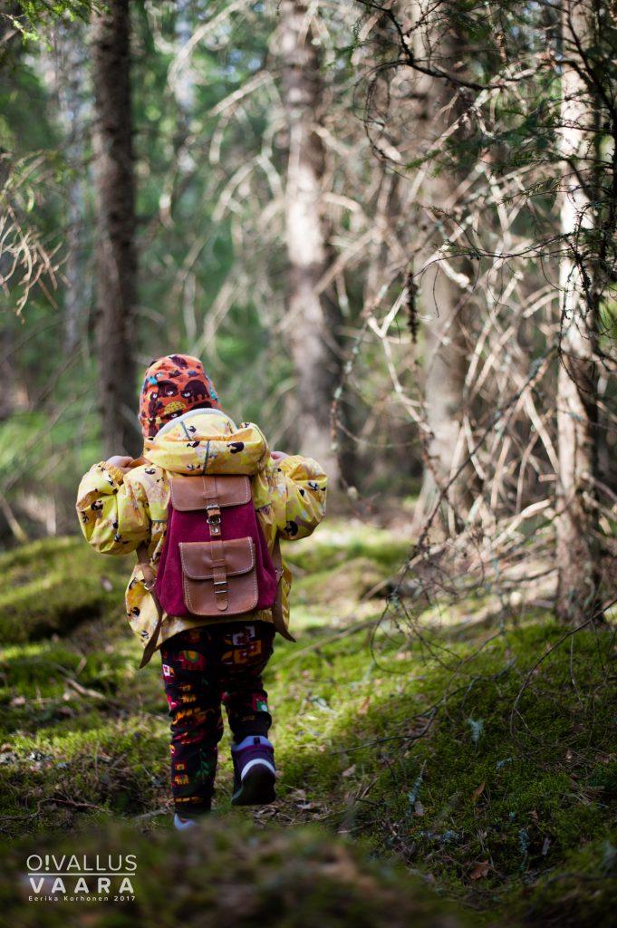 Lapsi reppu selässä kuusimetsässä.