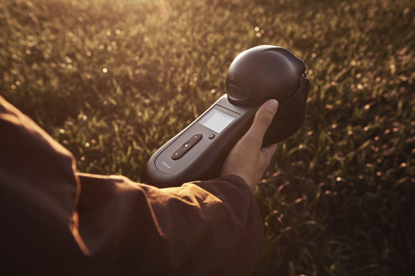 GrainSense-analysaattori kädessä, peltokasvillisuutta.