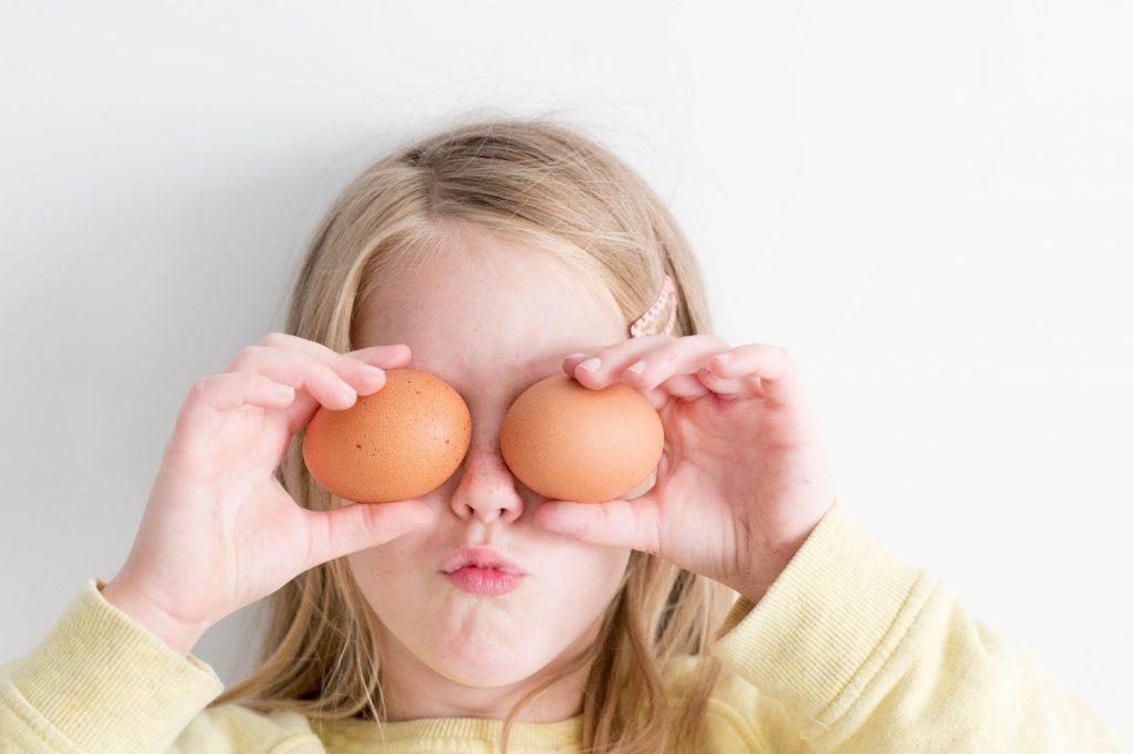 Kuvituskuva: Lapsi pitää kananmunia silmien edessä.