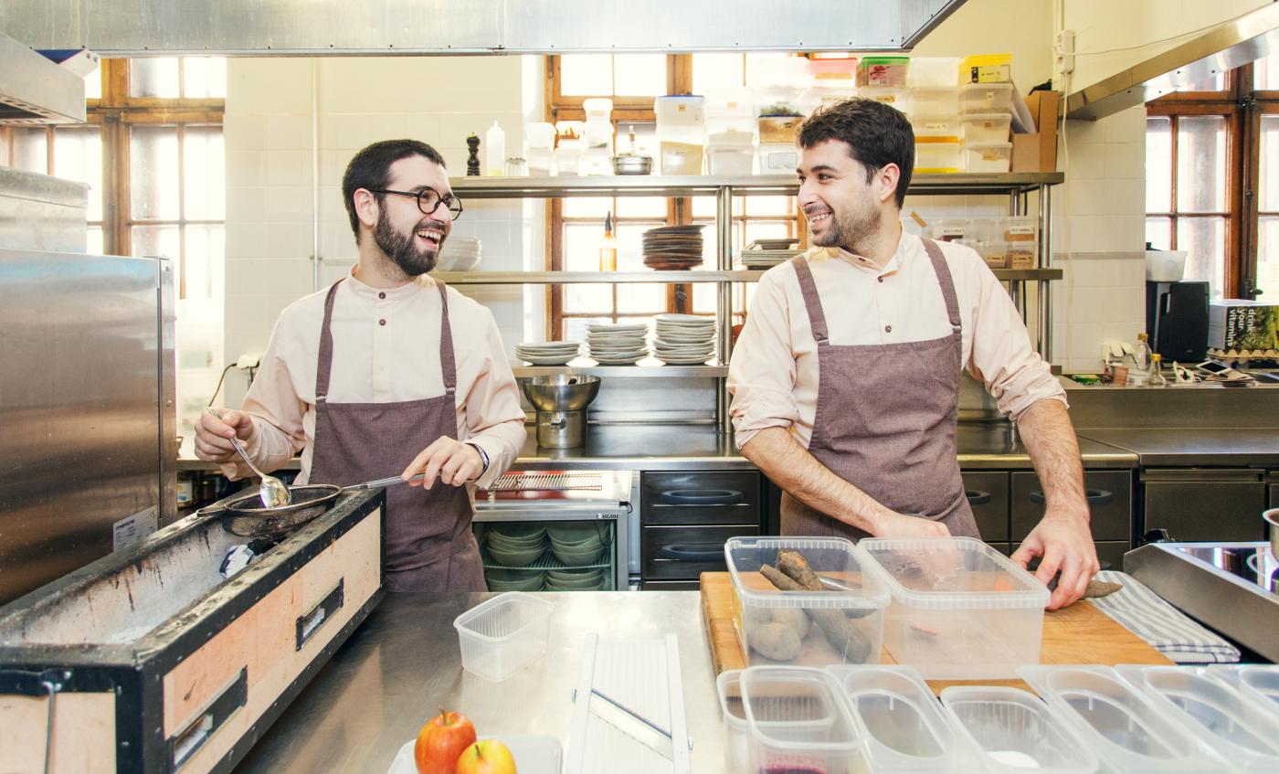 Kaksi kokkia työskentelemässä ravintolakeittiössä.