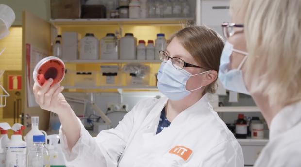 Tutkija esittelee punaista biopohjaista väriä kollegalleen laboratoriossa.