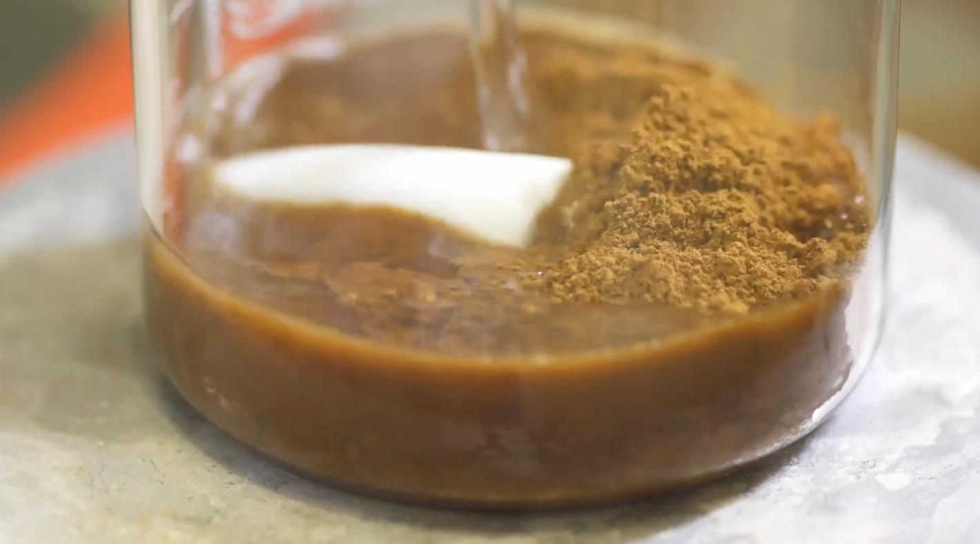 Ruskean ligniinijauheen sekaan kaadetaan vettä läpinäkyvässä lasissa.