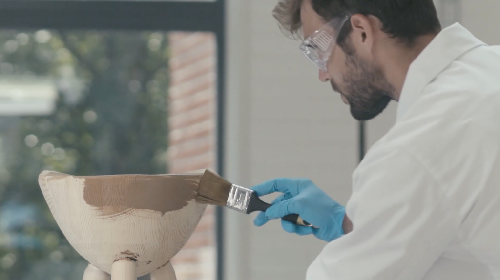 Valkoiseen laboratoriotakkiin pukeutunut mies levittää pensselillä ruskeaa puunsuoja-ainetta puutuotteeseen.